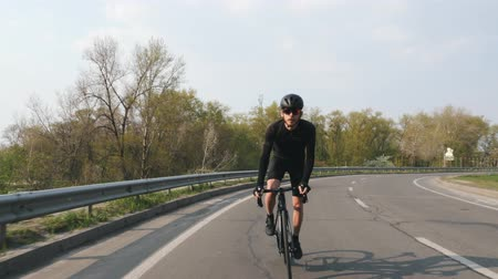 jarse : Focused Cyclist on a road bicycle riding towards camera at sunset. Biker wearing black jersey and shorts. Cycling concept. Slow motion Stok Video