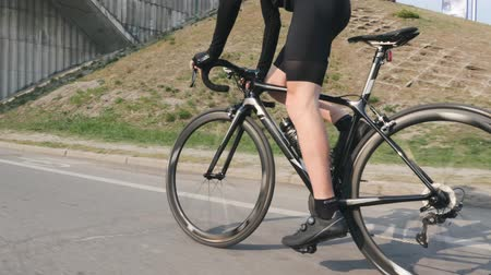 carbono : Professional cyclist riding bicycle out of the saddle. Side close up view of leg muscles in motion. Pedaling technique on bicycle. Cycling concept. Slow motion Archivo de Video