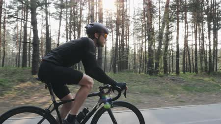racers : Close up shot of cyclist pedaling bike wearing black jersey, shorts, helmet and sunglasses. Back road carbon bicycle in the park. Stock Footage