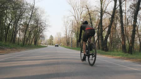 bicycle : Strong confident triathlete riding bicycle in the park. Back follow shot. Triathlon concept. Stock Footage