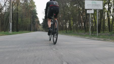 racers : Cyclist pedaling on bicycle close up leg muscle view. Bike rider in the park wearing black sportswear. Slow motion Stock Footage