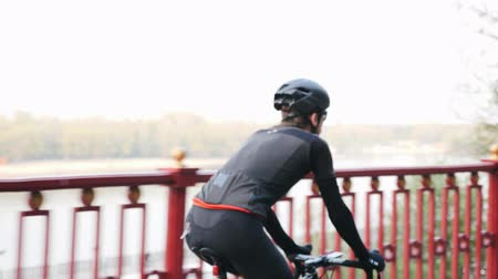 back side : Recreational cycling concept. Cyclist on bicycle back side follow shot. River on the background. Slow motion Stock Footage