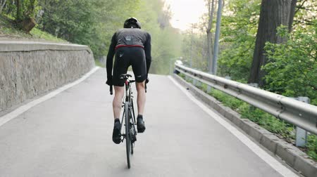 sela : Strong cyclist wearing black outfit riding uphill out of the saddle. Cycling training. Road bike. Slow motion
