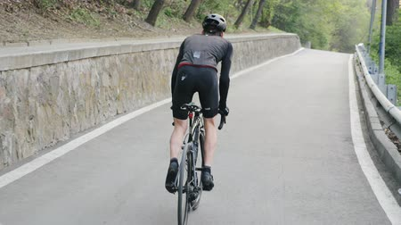 sela : Fit focused cyclist pedaling bicycle out of the saddle uphill. Strong legs with muscles pedaling. Uphill training for a cycling race. Vídeos