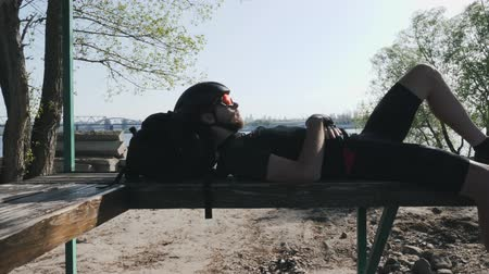 racers : Fit skinny cyclist resting on bench before training. Cyclist in black outfit lying on the bench with head on backpack. City and river on background