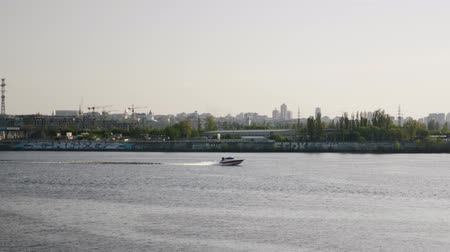 моторная лодка : Fast motorboat floating across the river. Side follow shot. Motorboat on the city river.