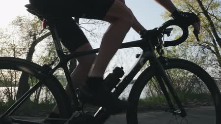 racers : Fit skinny cyclist close up pedaling and changing gears. Strong leg muscles spinning pedals. Cycling training. Slow motion