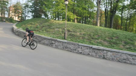 racers : Strong athletic cyclist sprinting uphill out of the saddle. Bike rider ascending hill wearing black sportswear.
