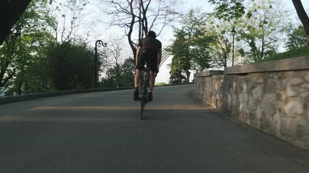 yarışçı : Strong professional cyclist rides uphill out of the saddle. Strong athletic leg muscles pedaling bike. Slow motion