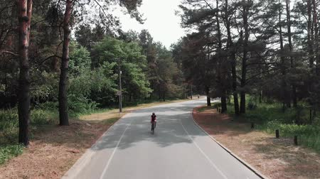 легкий : Confident focused young attractive girl is training on her bicycle in the park. Triathlon concept. Frontside follow shot. Стоковые видеозаписи