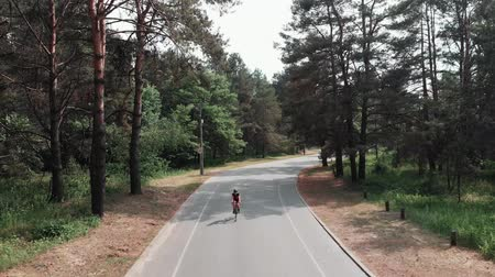 facil : Female cute cyclist wearing pink outfit and black helmet rides a bicycle in the park as a part of her training routine. Cycling concept. Frontside drone view. Archivo de Video