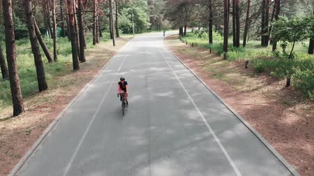 facil : Young attractive sportive woman in a pink jersey and a black helmet is enjoying her riding on the bike in the summer forest. Drone view.