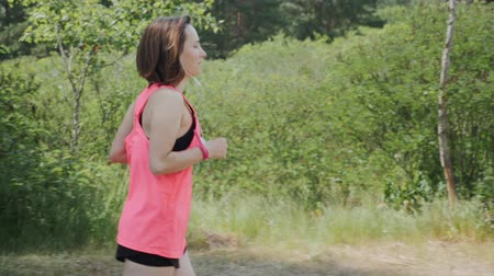 激しい : Brunette attractive girl in headphones and pink shirt running in park. Sportive woman training in park. Girl with funny sun tan running in forest. Running concept 動画素材