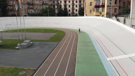fixní : Young attractive female road cyclist is riding at the velodrome. Girl on cycling track. Cycling concept. Drone view Dostupné videozáznamy