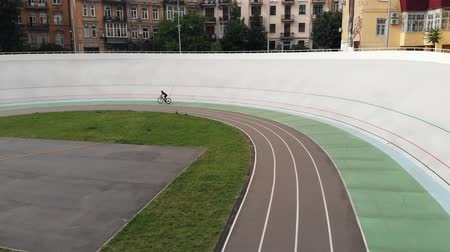 fixní : Aerial view of velodrome. Sportive girl at velodrome. Female cyclist riding road bike at cycling track. Cycling concept. Aerial drone view