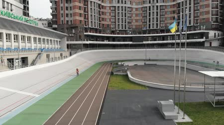 fixní : Young male cyclist is training at velodrome. Sportive boy is riding at cycling track. Aerial drone view of velodrome. Cycling concept Dostupné videozáznamy