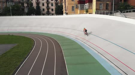 rögzített : Young track cyclist is training at open velodrome. Aerial drone view of cycling track. Training at velodrome in Kyiv