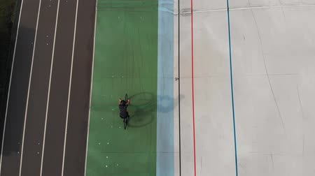 fixní : Velodrome In Kiev. Girl on road bike riding at Open Velodrome. Drone top view of female cyclist on cycling track.