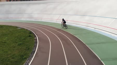 fixní : Attractive girl on road bike is riding on bicycle path at velodrome. Young sportive woman training at cycling track