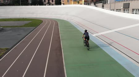 fixní : Female cyclist on road bike is training at velodrome. Close up of sportive girl on bike at cycling track. Training at velodrome