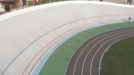 fixní : Young cyclists on fixed gear bike are cycling at velodrome. Drone view of professional cyclists are pedaling at cycling track. Cycling concept Dostupné videozáznamy