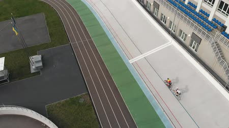 fixní : Drone top view of Kyiv velodrome with cyclists on fixed gear bikes. Fixed gear riders are training hard at cycling track. Aerial view of young cyclists preparing for race at velodrome in Kyiv Dostupné videozáznamy