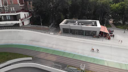 fixní : Aerial drone view of professional cycling team doing exercises at velodrome. Young trained cyclists riding at cycling track in Kyiv. Drone shot of velodrome