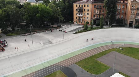 fixní : Drone flies near velodrome in Kyiv. Aerial view of caucasian male cyclists training at cycling track. Cyclist on fixed gear bike. Cycling concept