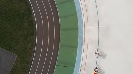 fixní : Professional cyclists training at velodrome. Boys on fixed gear bikes riding on cycling track. Cycling concept. Drone top view Dostupné videozáznamy