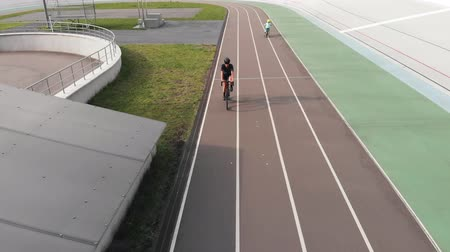 rögzített : Drone shot view of velodrome in Kyiv. Young female cyclist riding at cycling track. Child is riding at cycling path. Training at velodrome