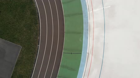 fixní : Professional sportive male cyclists on fixed gear bikes pedaling at velodrome. Drone top view of velodrome with cyclists. Cycling team training on cycling track Dostupné videozáznamy