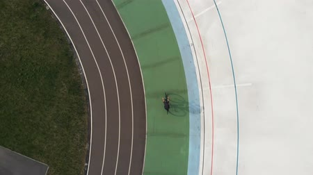fixní : Drone top view of female cyclist on road bike training at velodrome. Young cycling girl is riding slowly on cycling path at velodrome. Cycling concept Dostupné videozáznamy