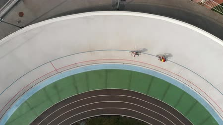 fixní : Drone top view of cycling competition at velodrome. Strong cyclists on track bikes competing on cycling track. Training at velodrome Dostupné videozáznamy