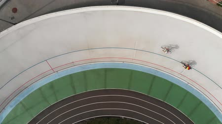 fixní : Drone top view of professional cyclists competing on velodrome. Young male cyclists on fixed gear bikes training on cycling track. Race at velodrome