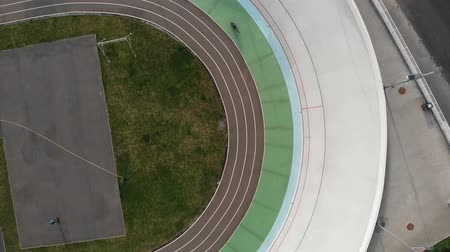 fixní : Velodrome in Kyiv from birds eyes view. Young motivated girl training at velodrome. Sportive cute woman on road bike riding on cycling track Dostupné videozáznamy