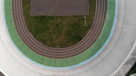 fixní : Aerial drone view of cycling track with two cyclists. Strong male cyclists training at velodrome. Drone top view of velodrome in Kiev Dostupné videozáznamy