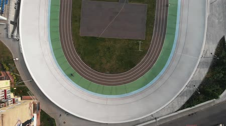 fixní : Young sportive female cyclist learning to ride on open cycling track. Open velodrome from birds eyes view. Cycling concept