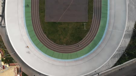 fixní : Velodrome from birds eyes view. Strong professional male cyclists on fix gear bikes riding on cycling track. Training at velodrome. Race at velodrome