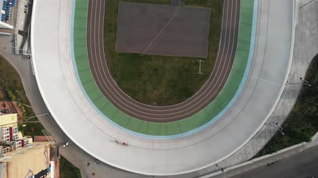 fixní : Professional track cyclists training at velodrome. Young strong men competing on cycling track. Workout training at velodrome. Drone view of velodrome Dostupné videozáznamy