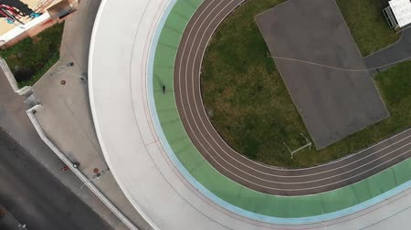 fix : Drone flies around velodrome. Attractive girl on road bike riding on cycling track. Professional cyclists training at velodrome. Cycling concept