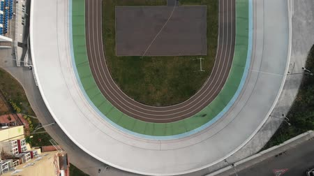 fixní : Aerial drone view of cycling track. Young sportive cyclists training at velodrome. Girl on road bikes learning to ride on cycling track. Strong male cyclists riding at velodrome