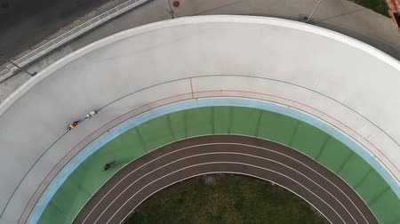 rögzített : Close up drone view of strong cyclists training at velodrome. Young girl on road bike riding on cycling track. Drone top view of cyclists at velodrome