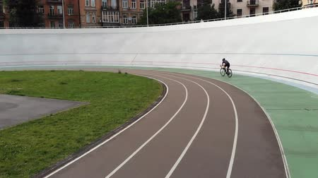 fixní : Young attractive female cyclist training at velodrome. Sportive girl in helmet riding on cycling track. Woman on road bike learning to ride