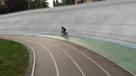 fixní : Slim sportive cycling girl on track bicycle is training at velodrome. Attractive woman on road bike riding on cycling track. Aerial view of velodrome Dostupné videozáznamy