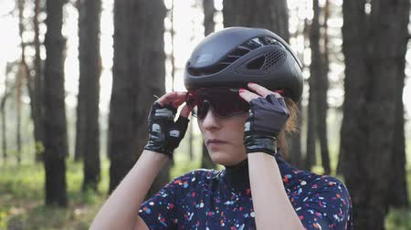 hosenträger : Portrait of young attractive girl putting glasses on before cycling wearing black helmet and blue jersey. Cycling Concept. Slow motion