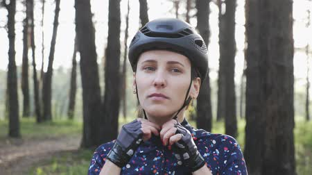 jarse : Confident young cyclist woman puts on helmet looking to the camera. Triathlon Concept. Slow motion Stok Video