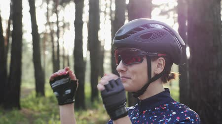 hosenträger : Portrait of happy triathlete girl putting off cycling glasses wearing black helmet. Cycling concept