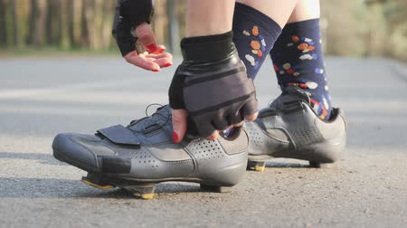 aparat ortodontyczny : Cyclist girl tightens road shoes before the bicycle ride. Close up