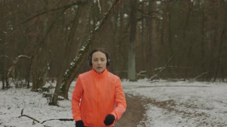 motivováni : Woman puts on headphones and starts running in park. Young motivated female doing outdoor fitness exercises as part of daily workout. Fit focused professional runner athlete hard training in forest