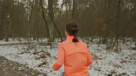 rajstopy : Woman runs in park. Female is training offseason. Girl in orange jacket and blue tights jogging outdoor. Professional athlete preparing for marathon and doing cardio workout exercises. Trail run